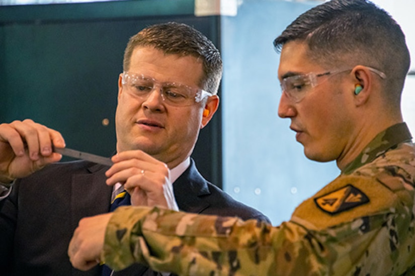 Two men, one in a military uniform, look at a small metal ruler.  Both wear safety glasses.