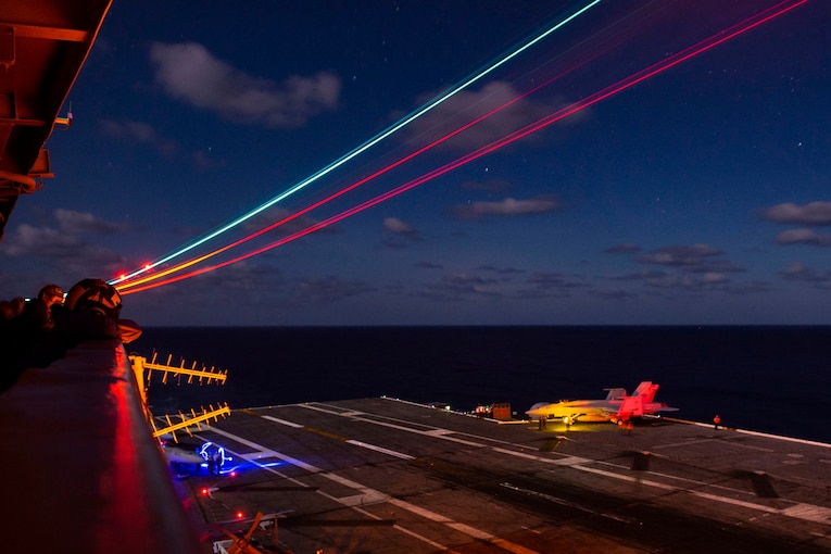 Sailors watch an aircraft on a flight deck at night, illuminated by colored lights.