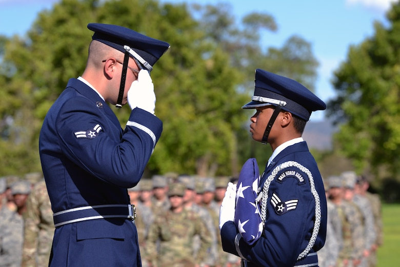 U.S. Air Force Airman 1st Class Quinten Avila, left, 377th Air Base Wing Honor Guard member, salutes the U.S. flag being held by U.S. Air Force Senior Airman Tatyana Howard, 377th ABW HG member, during a 9/11 retreat ceremony at Kirtland Air Force Base, N.M., Sept. 11, 2019. The retreat ceremony was held to honor and remember the nearly 3,000 people that died in the attacks on 9/11 and for those that have been killed in defense of the country since that day. (U.S. Air Force photo by Staff Sgt. Dylan Nuckolls/Released)