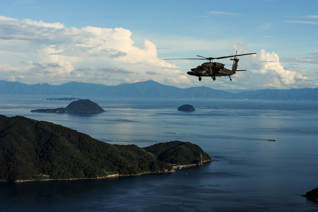 A helicopter flies over blue waters studded with wooded islands.