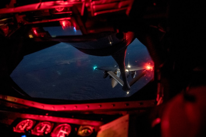A military jet prepares for an aerial refueling at night.