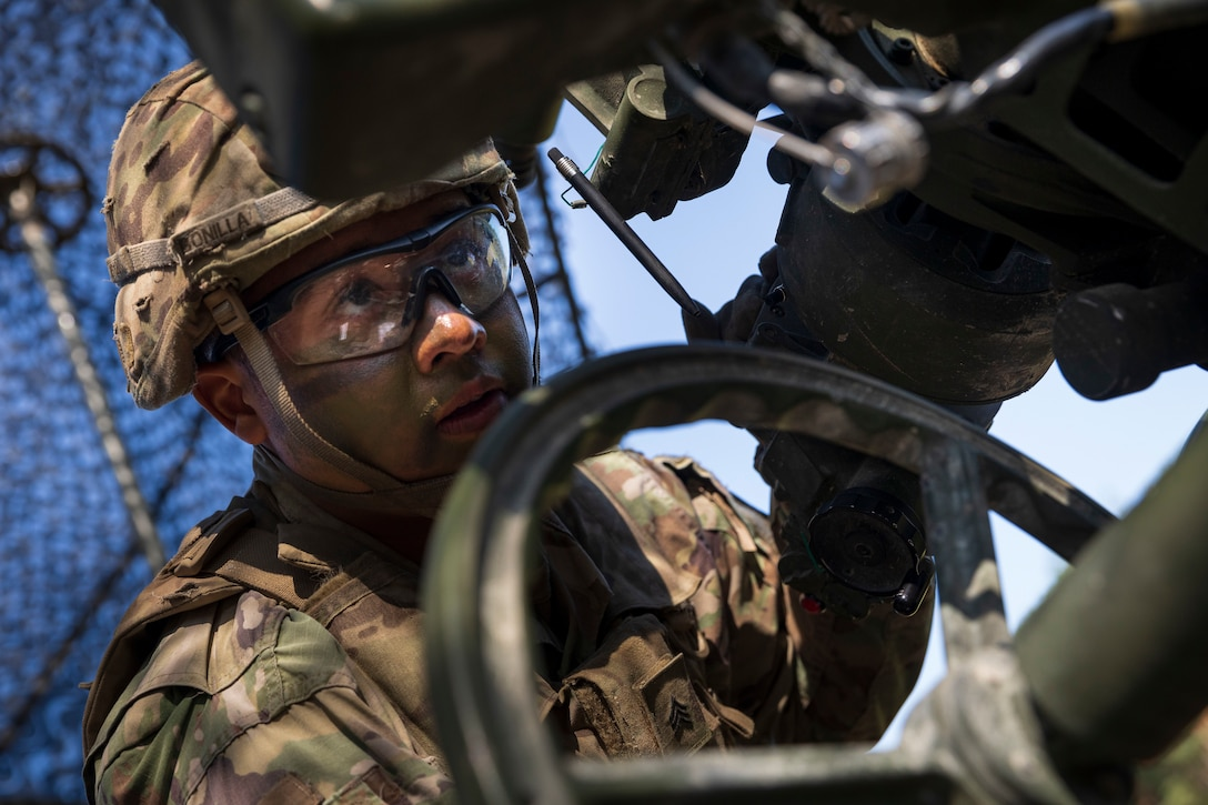 A soldier focuses his eyes on part of a large military weapon.