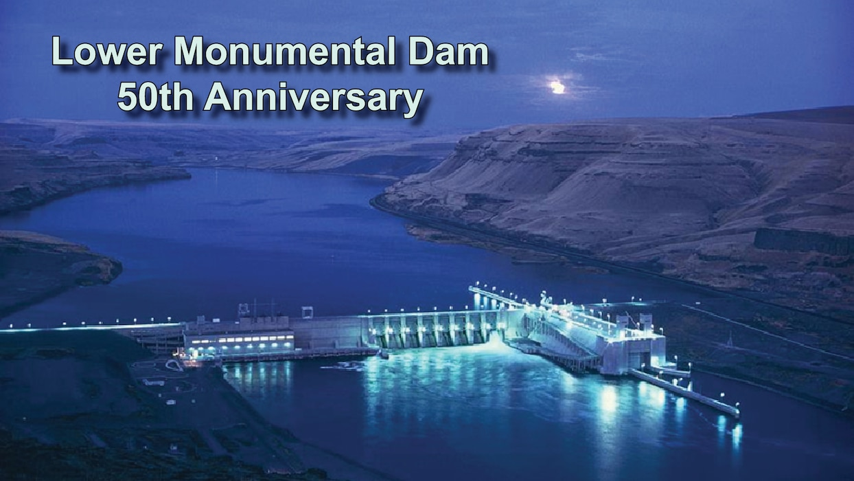 a shot of lower monumental dam at night with the lights shining blue on the water. Text above reads Lower Monumental Dam 50th Anniversary