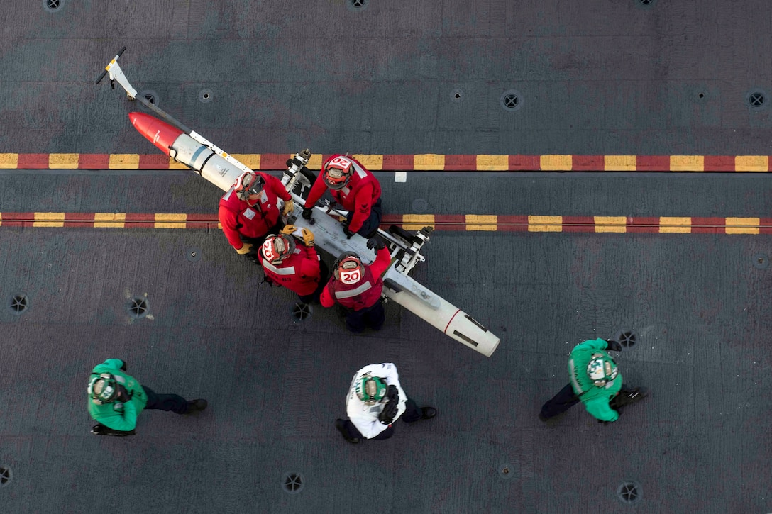 Four sailors in red, seen from overhead, maneuver a missile on a deck, as three other sailors walk by.