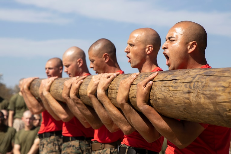 Five Marines stand in a row as they carry a big log.