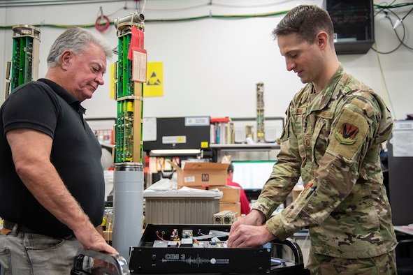 Doug Dale (left), 709th Support Squadron flight chief, and Master Sgt. Joseph King, 709th SPTS Central Repair Facility superintendent, work on a device that converts and combines multi-serial signals into a single data stream for the Air Force Technical Applications Center, Patrick AFB, Fla.  Dale and his team developed a solution to dramatically increase AFTAC's Geophysical Field System sparing posture worldwide.  (U.S. Air Force photo by Matthew S. Jurgens)