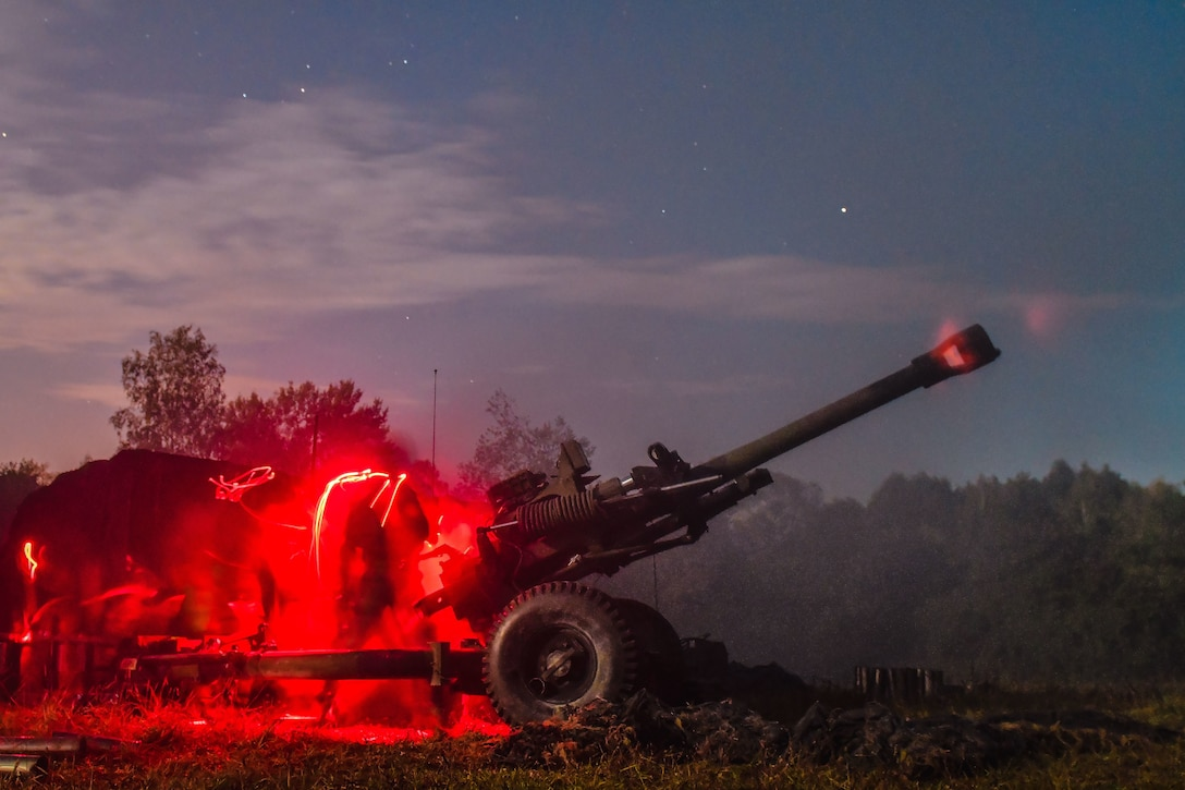 Paratroopers fire a howitzer at night causing a red glow around the gun.