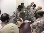 A New Jersey Army National Guard Soldier discusses a Tactical Combat Casualty Care (TCCC) scenario with members of the Qatari Emiri Land Forces (QELF) Sept. 8 -12, 2019, at the Qatar Emiri Land Force Artillery School in Al Rayyan Municipality, Qatar. The weeklong event, a part of the National Guard Bureau's State Partnership Program, provided an opportunity to share best life saving practices with the QELF.