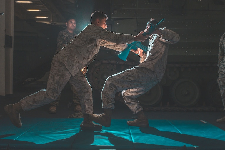 Two Marines practice martial arts in a dark room.