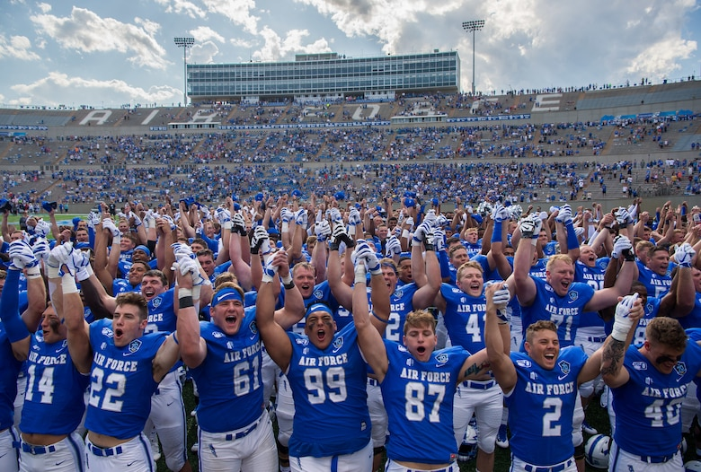 U.S. Air Force Academy football players raise their hands in victory