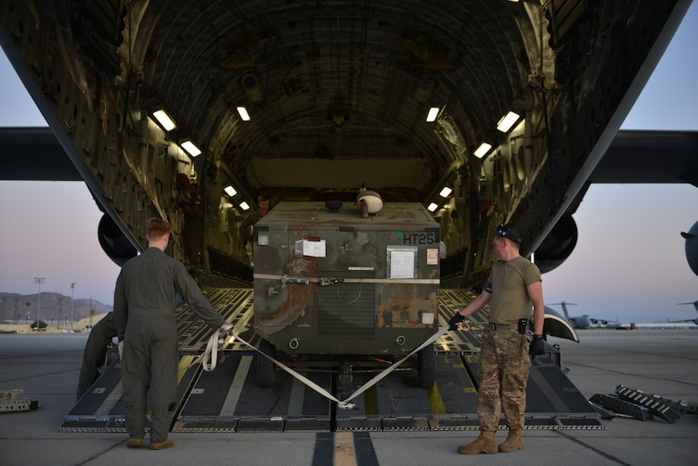 An Air Force Reserve Airman from March Air Reserve Base, California, assists an active duty Airman from Fairchild Air Force Base, Washington, with unloading cargo from a C-17 Globemaster III from Joint Base Lewis-McChord, Washington, Sept. 4, 2019. Fairchild Airmen will continue their Global Reach mission at March ARB during Air Mobility Command's premier exercise Mobility Guardian 2019, currently hosted at Team Fairchild. Through Total Force Integration, Mobility Airmen are capable of accomplishing even more through building strong relationships and interoperability. (U.S. Air Force photo by Airman 1st Class Ryan Gomez)
