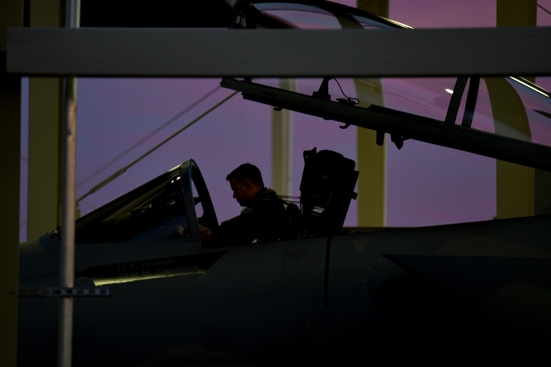An Air Force pilot, shown in silhouette, sits in an open cockpit in a hangar-type structure, against a purple sky.