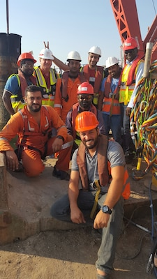 Photo of 8 construction workers in a group shot. One is being given the rabbit ears gesture used in photos.