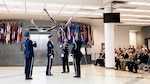 Members of the Air Force Honor Guard Drill Team toss bayonets during their performance as audience watches.