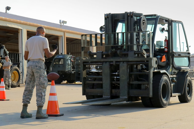 Senior Airman Samuel Lee, 72nd Aerial Port Squadron aerial transportation specialist, directs a forklift during a rodeo, Sept. 6, 2019, at Tinker Air Force Base, Oklahoma. The rodeo incorporated various jobs competed by aerial port in a fun and competitive atmosphere. (U.S. Air Force photo by Senior Airman Mary Begy)
