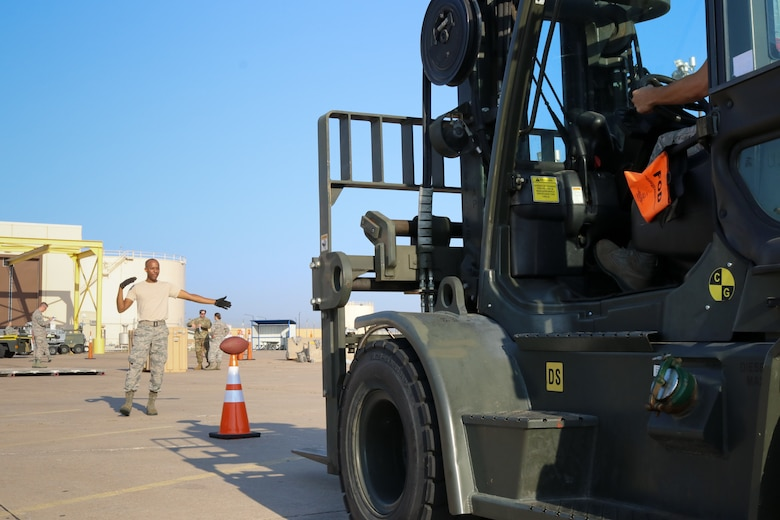 Senior Airman Samuel Lee, 72nd Aerial Port Squadron aerial transportation specialist, directs a forklifft during a rodeo, Sept. 6, 2019, at Tinker Air Force Base, Oklahoma. The rodeo incorporated various jobs competed by aerial port in a fun and competitive atmosphere. (U.S. Air Force photo by Senior Airman Mary Begy)