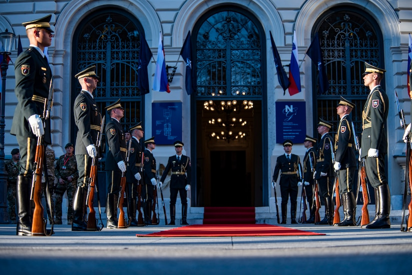 Troops flank a red carpet outside an ornate building entrance.