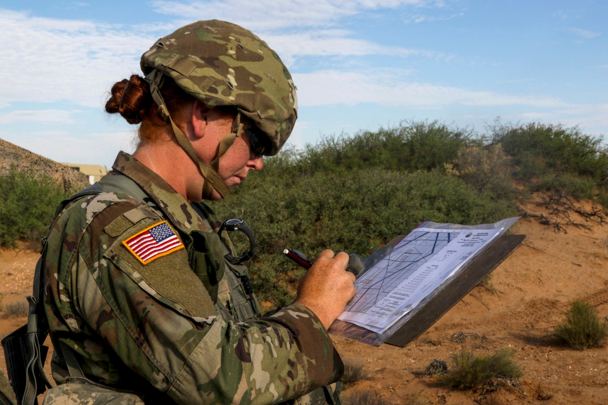 A soldier studies a map in a grassy area.