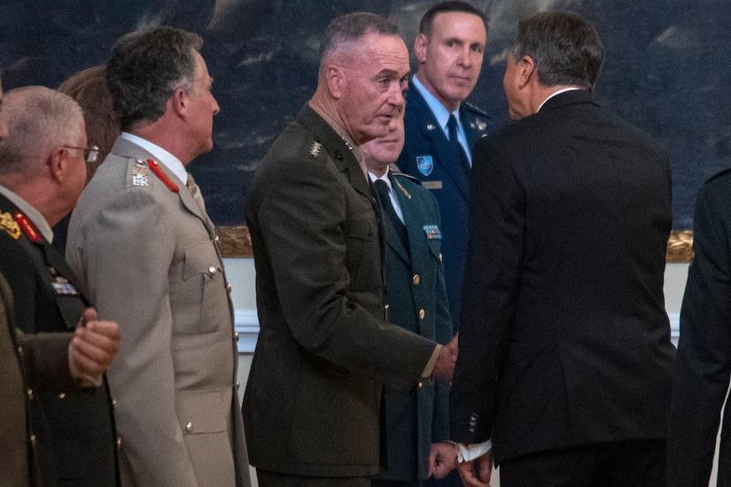 General and civilian shake hands.
