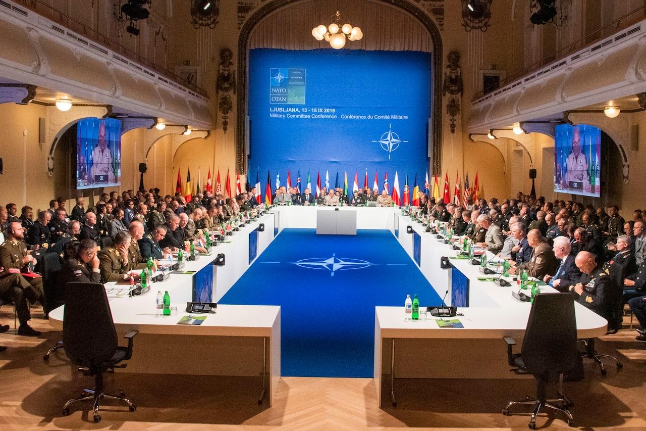 Military leaders sit around huge room