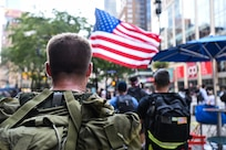 Tech. Sgt. Joshua Schmitz, 818th Mobility Support Advisory Squadron survival, evasion, resistance and escape specialist, looks at the American flag while marching towards ground zero in New York City Sept. 11, 2019. Volunteers participated in a 100 mile ruck march from Joint Base McGuire-Dix-Lakehurst, New Jersey to the 9/11 Memorial in remembrance of the attacks 18 years ago.   Throughout the 100 miles, participants took turns carrying a prisoner of war/missing in action flag along with an American flag that served in Afghanistan to commemorate the individuals who lost their lives during the attacks. (U.S. Air Force photo by Airman 1st Class Ariel Owings)
