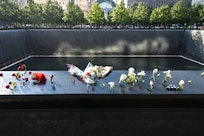 Family members placed flowers on the engraved names of the Sept. 11 memorial in New York City Sept. 11, 2019. People come from all over the world to pay their respects to the fallen individuals and their families from the attacks of Sept. 11, 2001. Two waterfalls were built in place of the twin towers as a memorial to the 2,977 people killed, with each name engraved in the stone. (U.S. Air Force photo by Airman 1st Class Ariel Owings)