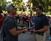 U.S. Air Force Maj. Jon Leetch, Columbus Air Force Base, Miss. 41st Flying Training Squadron instructor pilot, hands off an American flag to Paul Vorbeck, 9/11 Memorial and Museum director of security, after the 100 mile ruck from Joint Base McGuire-Dix-Lakehurst, New Jersey to New York City Sept. 11, 2019. Throughout the 100 miles, participants took turns carrying a prisoner of war/missing in action flag along with an American flag that served in Afghanistan to commemorate the individuals who lost their lives during the attacks. (U.S. Air Force photo by Airman 1st Class Ariel Owings)