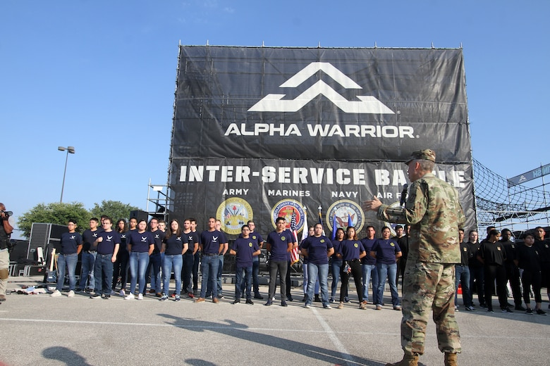 AFIMSC Commander Maj. Gen. Tom Wilcox talks to new recruits for the Air Force, Navy and Army about the importance of the oath of enlistment during the opening ceremonies of the 2019 Alpha Warrior Inter-Service Battle Sept. 14, 2019, at Retama Park, Selma, Texas. Following his remarks, the general administered the oath to the new Airmen. Senior leaders for the U.S. Navy and U.S. Army then did the same for their respective new recruits. (U.S. Air Force photo by Annette Strapple)