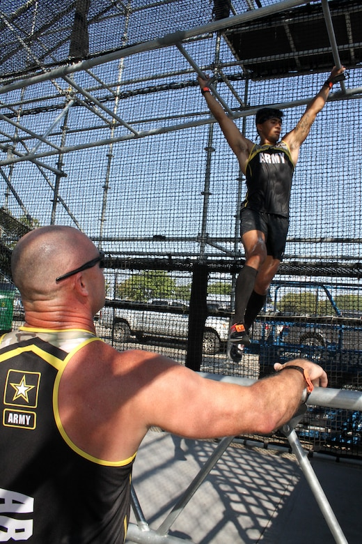 "U.S. Army 2nd Lt. Chris Gabayan crosses lower level bars in ""Alacatraz"" while Sgt. 1st Class Aaron Martin cheers him on during the 2019 Alpha Warrior Inter-Service Battle Sept. 14, 2019, at Retama Park, Selma, Texas. Alcatraz  is the last of more than 30 obstacles on the course. At the end of this year's competition, the U.S. Air Force earned a repeat victory over the Army and the U.S. Navy. (U.S. Air Force photo by Debbie Aragon)"