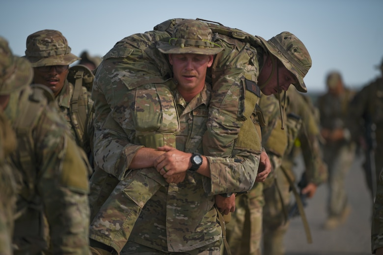 Senior Airman Daniel Pierce, 90th Ground Combat Training Squadron training instructor, carries Senior Airmen Dakota Cornett, 341st Security Support Squadron tactical response force member, while rucking at the Nuclear Advanced Designated Marksman course, at Camp Guernsey, Wyo., Sept. 29, 2019. During the ruck they simulated casualties to see how members would adapt to reach their objective. (U.S. Air Force photo by Staff Sgt. Ashley N. Sokolov)
