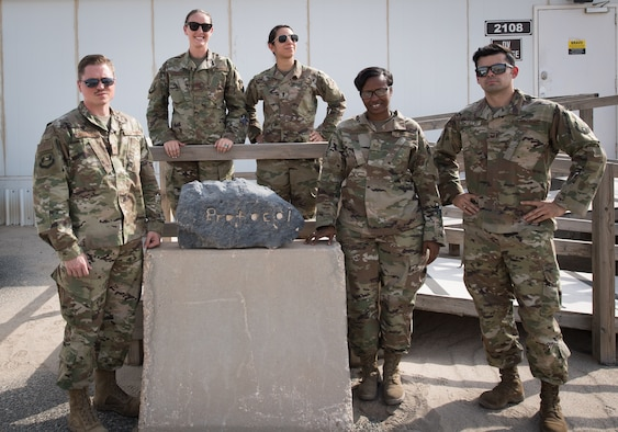 The 386th Air Expeditionary Wing protocol team poses for a photo outside their office at Ali al Salem Air Base, Kuwait, Aug. 15, 2019. Left to Right: Tech. Sgt. Tyler Shepherd, NCO-in-charge of protocol, deployed from Moody Air Force Base, Georgia; Capt. Rosa-Mae Bacon, chief of protocol, deployed from Davis-Monthan AFB, Arizona; 1st Lt. Kassandra Prusko, deputy chief of protocol, deployed from Andrews AFB, Maryland; Staff Sgt. Courtney Lansden, protocol specialist, deployed from Offutt AFB, Nebraska; and Tech. Sgt. Diego Casillas, superintendent of protocol; deployed from Los Angeles AFB, California. (U.S. Air Force photo by Tech. Sgt. Daniel Martinez)