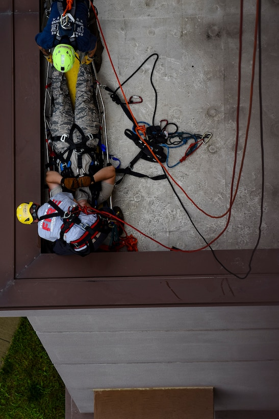 Pacific Air Forces firefighters secure a simulated victim into a stokes basket during a Department of Defense Rescue Technician course, Sept. 9, 2019, at Osan Air Base, Republic of Korea. Instructors from Andersen Air Force Base, Guam's 554th RED HORSE Squadron trained and tested 10 Pacific Air Forces firefighters from three bases on high-risk, elevated and confined space rescue tactics. (U.S. Air Force photo by Staff Sgt. Greg Nash)