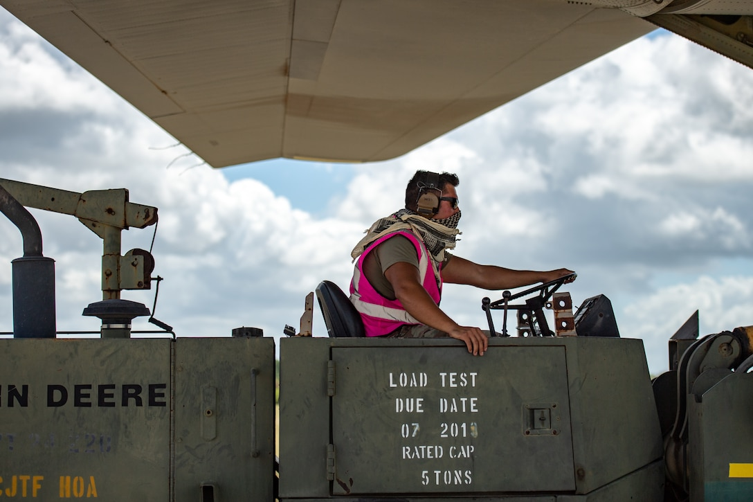 U.S. Air Force Tech. Sgt. Gary Yates, 475th Expeditionary Air Base Squadron air operations noncommissioned officer in charge, downloads cargo at Camp Simba, Kenya, Aug. 26, 2019. Yates worked with the 75th Expeditionary Airlift Squadron aircrew who delivered the cargo to Camp Simba. (U.S. Air Force photo by Staff Sgt. Devin Boyer)