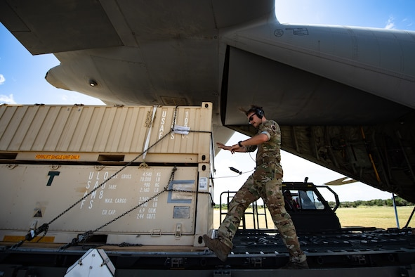 U.S. Air Force Staff Sgt. Alek Gorohoff, 75th Expeditionary Airlift Squadron instructor loadmaster, downloads cargo at Camp Simba, Kenya, Aug. 26, 2019. The 75th EAS provided airlift while the 475th Expeditionary Air Base Squadron operated vehicles to download the cargo. (U.S. Air Force photo by Staff Sgt. Devin Boyer)