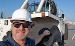 Ben Stoline, a forklift mechanic for DLA Distribution Norfolk, Virginia, remembers Hurricane Isabel's blow to his home and community 16 years later. Ben leans against a forklift.
