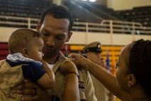 A U.S. Navy Sailor holds his child as he is pinned with chief anchors by his wife during the Chief Petty Officer Pinning Ceremony on Camp Lejeune, N.C., Sept. 13, 2019. Thirty-three chief selects were pinned to the rank of chief petty officer and among them were two Marines that earned the title of honorary chief petty officer. Before the chief selects can pin on their new rank, they must go through a six-week initiation course in order to instill the trust that is inherent with the donning of the uniform of a chief. (U.S. Marine Corps photo by Cpl. Leynard Plazo)