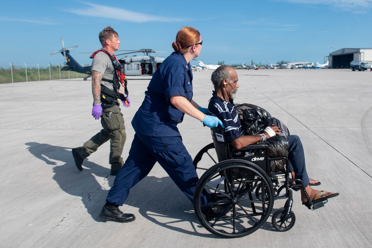 A service member pushes a man in a wheelchair on a flightline as another service member walks beside her.