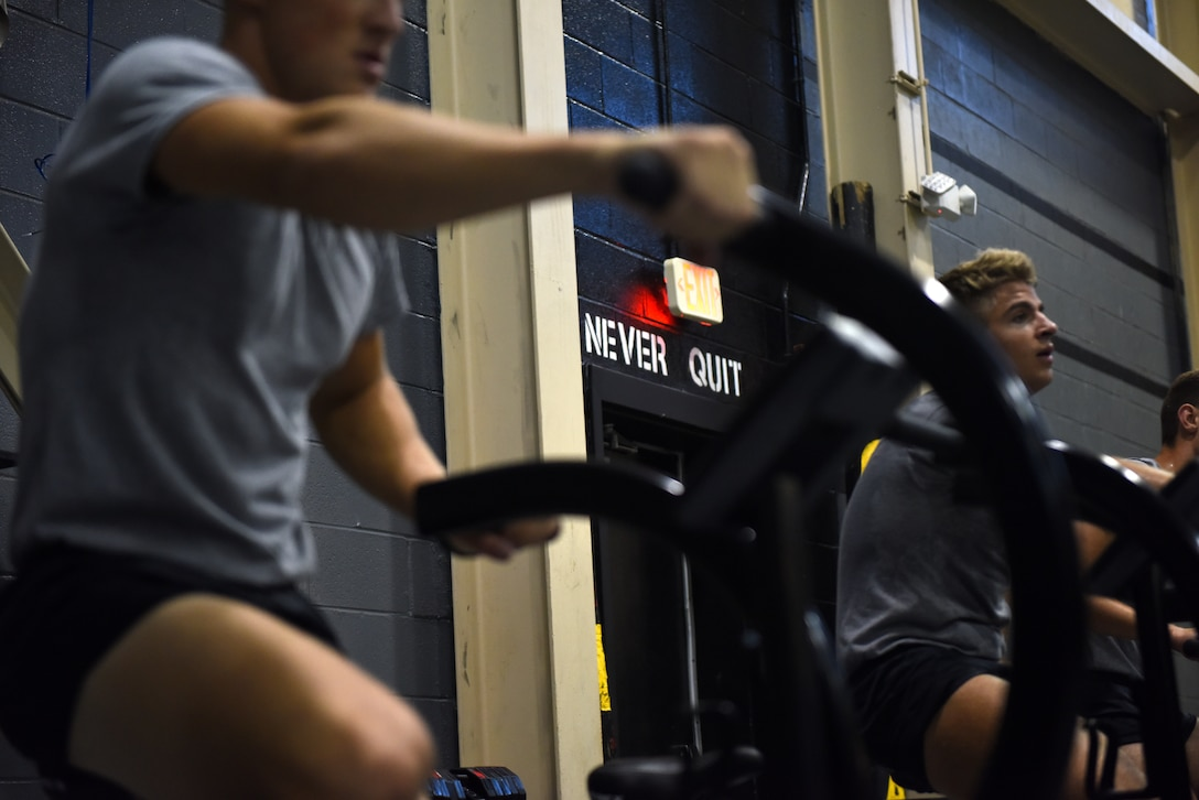 Airmen from the 352nd Special Warfare Training Squadron exercise on workout bikes at Matero Hall on Keesler Air Force Base, Mississippi, Aug. 22, 2019. Special Warfare trainees partake in intense physical training sessions to prepare them for combat. (U.S. Air Force photo by Airman Seth Haddix)