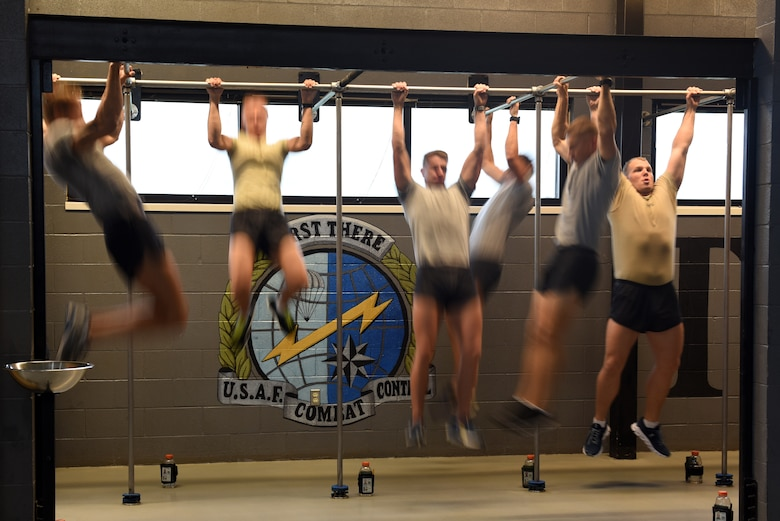 Airmen from the 352nd Special Warfare Training Squadron perform pull-ups at Matero Hall on Keesler Air Force Base, Mississippi, Aug. 22, 2019. Special Warfare trainees partake in intense physical training sessions to prepare them for combat. (U.S. Air Force photo by Airman Seth Haddix)