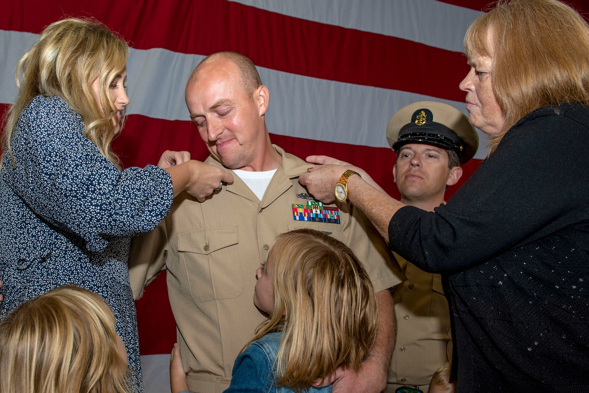 Two women affix shoulder pins to a sailor's uniform as he watches and hugs a girl.