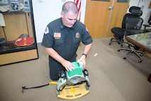 Assistant Fire Chief Greg Kunkel, Emergency Medical Services supervisor, MCLB Fire Department, slides the rechargeable lithium ion battery pack into a slot on the Lucas 2 automatic chest compression device. The yellow board at the bottom goes under the gurnery or board the patient is strapped to while the green piston goes over the top position on the sternum and delivers 110 compressions a minute, the CPR standard requirement. The $15,000 Lucas 2 can also be plugged into the ambulance power through and invertor port so it does not rely on the device battery