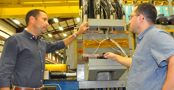 "IMAGE: DAHLGREN, Va. (Sept. 5, 2019) - Moises Iglesias – lead systems engineer for the electromagnetic railgun weapon system at Naval Surface Warfare Center Dahlgren Division (NSWCDD) – discusses railgun design considerations with his colleague, Pierre Avila, NSWCDD computer scientist.  ""A leader helps the organization, the team, and its members become famous - providing the tools, training, development, recognition and opportunities to deliver products that will help the organization and its members grow professionally and personally while establishing the organization's National Subject Matter Expertise and Recognition,"" said Iglesias, an avid runner and native of Carolina, Puerto Rico."