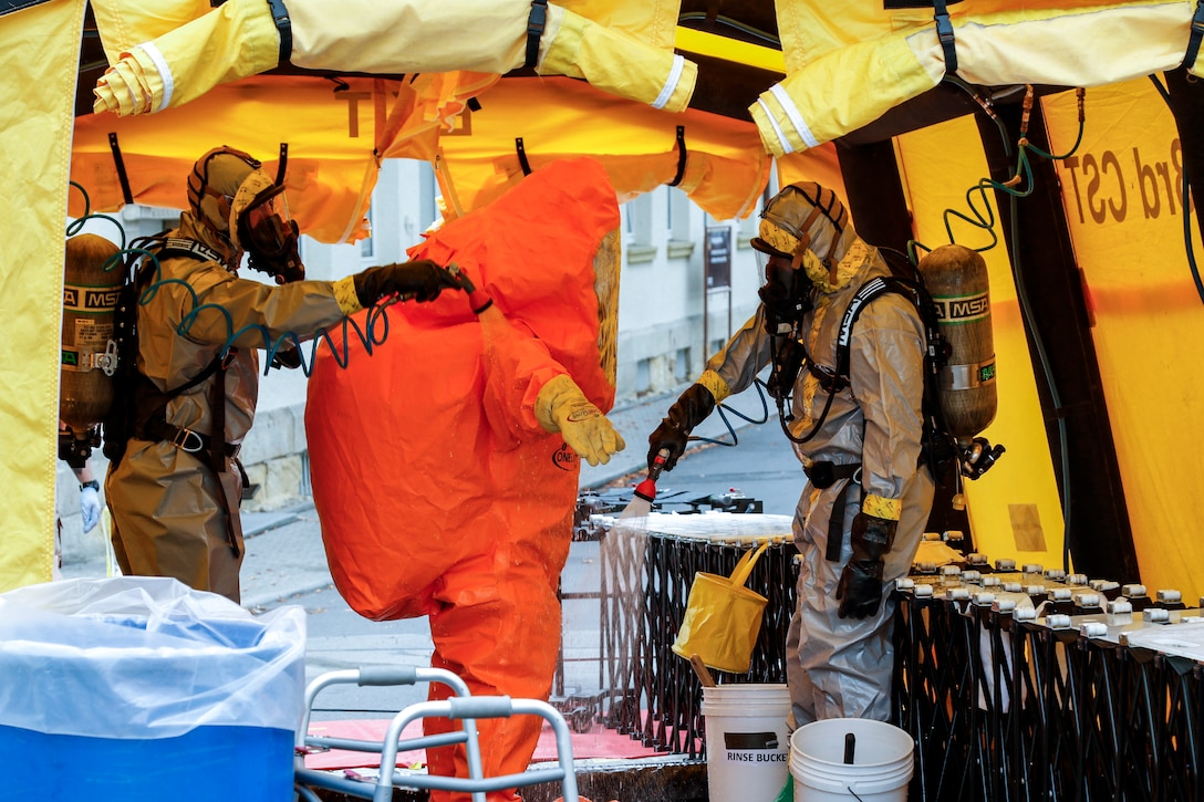 Soldiers in protective gear use instruments to manually scan someone in an orange protective suit.