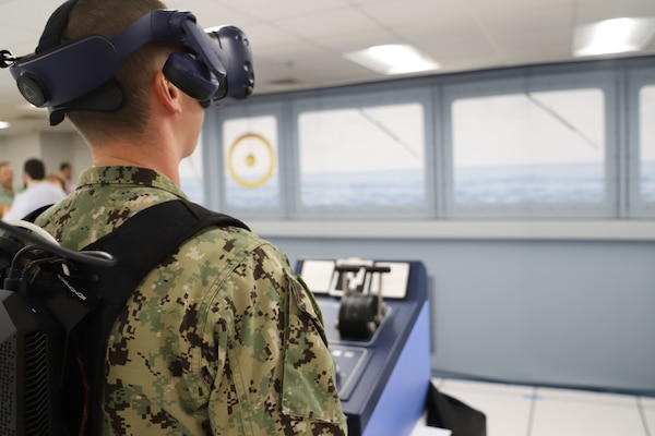 IMAGE: A Sailor from Tactical Training Group Atlantic stands in the helm position during an Advanced Navigation Team Shipboard Simulation Phase 1 system scenario in the command's Naval Simulation Center. The Sailor is observing the real world through the augmented reality headset.