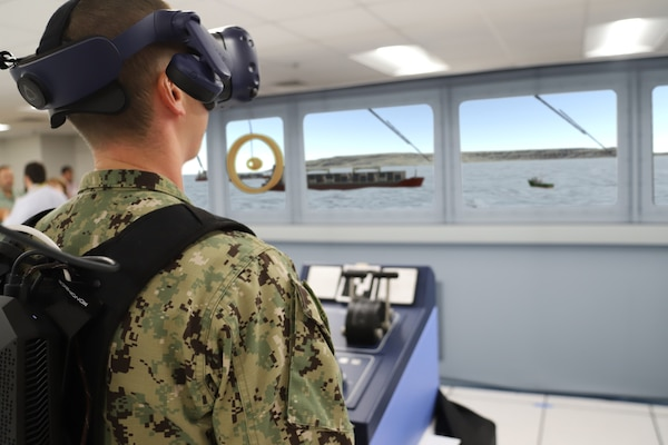 IMAGE: A Sailor from Tactical Training Group Atlantic stands in the helm position during an Advanced Navigation Team Shipboard Simulation Phase 1 system scenario in the command's Naval Simulation Center. The Sailor is observing the simulated world through the augmented reality headset.