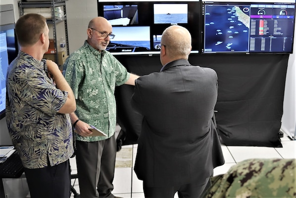 "IMAGE: Glenn White (center), Office of Naval Research, discusses Mentor Station ""real time"" data analytics to John Fiore, Naval Surface Warfare Center Dahlgren Division technical director. The briefing occurred during an Advanced Navigation Team Shipboard Simulation Phase 1 system demonstration in the command's Naval Simulation Center."