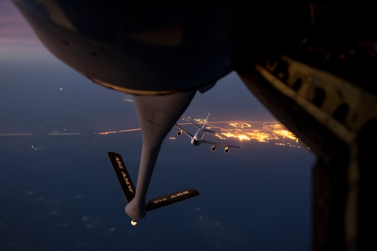 A large military aircraft approaches the back of another aircraft at night.