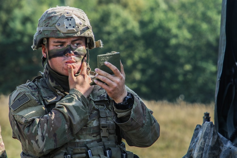 A soldier puts paint on his face while looking into a small mirror.