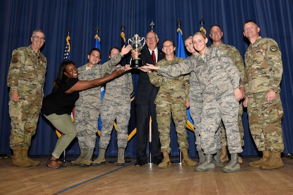 Gen. John Hyten, commander of U.S. Strategic Command, far left, Mr. Ken Stinson, chairman of Strategic Command Consultation Committee (SCC), middle, Col. Thomas Falzarano, commander of 21st Space Wing, second from right, and Chief Master Sgt. Patrick McMahon, far right, command senior enlisted leader of USSTRATCOM, present the Omaha Trophy to Airmen of the 21st Space Wing at Peterson Air Force Base, Colorado, Sept. 9, 2019. The 21st SW won the trophy for global operations, one of five official categories including intercontinental ballistic missile operations, strategic aircraft operations, strategic bomber operations and submarine ballistic missile operations. The Omaha Trophy was created by the SCC, located in Omaha, Nebraska, and presented to a unit of USSTRATCOM on behalf of the citizens of Omaha. It was first presented in 1971 and is given to the command's best wing as a token of recognition and appreciation. (U.S. Air Force photo by Staff Sgt. Alexandra M. Longfellow)