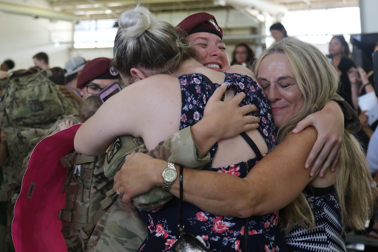 A soldier is embraced by members of her family.